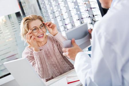 Rijpe oftalmoloog en vrouwelijke gepensioneerde die een glazen kiezen bij de opticaopslag Stockfoto