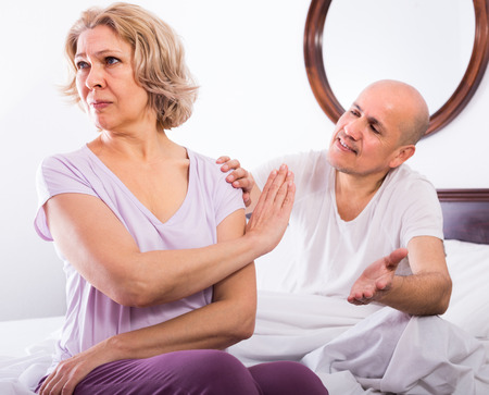impotent: Two mature spouses having domestic quarrel in bedroom Stock Photo