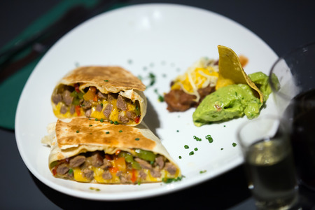 Mexican burrito with meat and beans filling served with guacamole