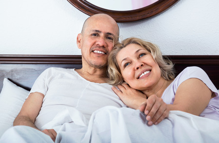 awaking: Positive happy smiling mature loving couple lounging in bed after awaking cuddling