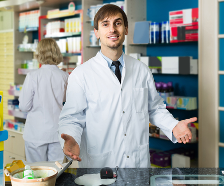 farmacy: Portrait of positive young english male pharmacists working in modern farmacy Stock Photo