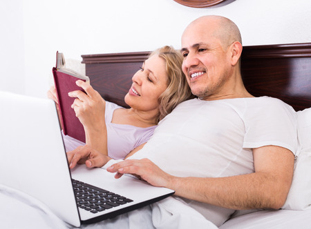 evening class: happy adults together reading news from notebook and smartphone  in bed Stock Photo