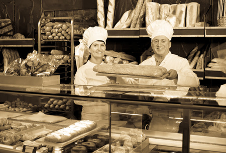 polite: Portrait of polite bakers with fresh bread smiling in bakery