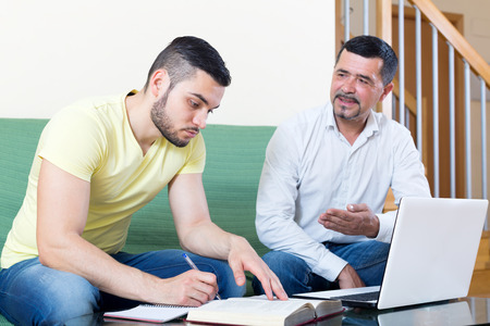 learning by doing: Smiling mature father helping adult son to do homework. Focus on the left man