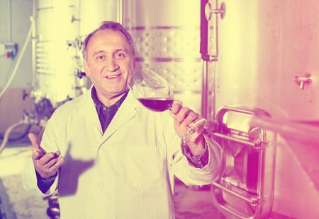 diligente: Diligente sonriendo vino controles fabricante de calidad de los vinos en la bodega