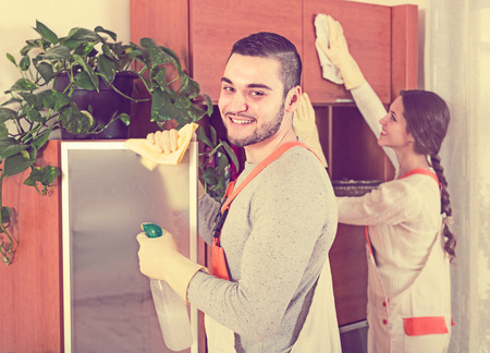 premises: Cleaning premises team working at clients home. Focus on man Stock Photo