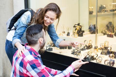 shopwindow: couple of tourists choosing wristwatch at shopwindow