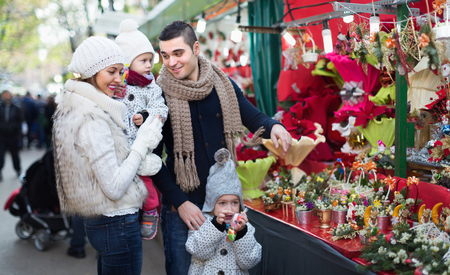 Happy parents and children buying red Euphorbia at Christmas fair. Focus on woman Stock Photo