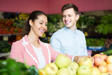 Positive young spouses choosing fruits and vegetables in market and smiling