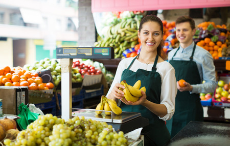 happines: Smiling young stuff in aprons selling sweet bananas at marketplace Stock Photo