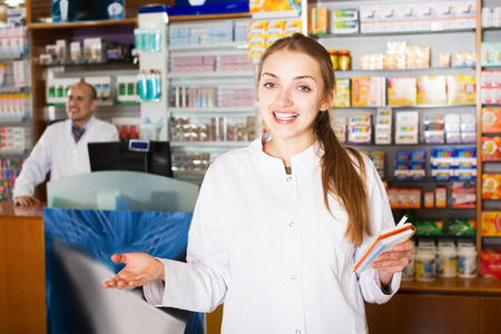 Team of pharmaceutist and technician working in pharmacy and smiling