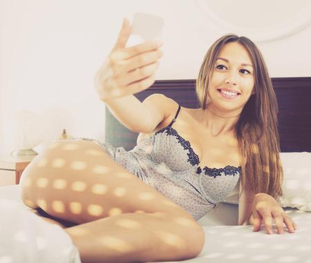 Jonge gelukkige Amerikaanse vrouw in lingerie het ontspannen in bed en het nemen van beeld met mobiele telefoon in ochtendzonlicht
