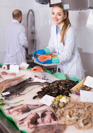 Mature european seller and young assistant offering fresh fish in shop