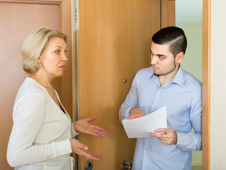 Agent trying to collect money from aged blonde housewife at home door