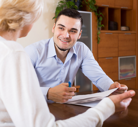 Mature woman and happy young fiance signing marriage settlement