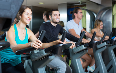 happy russian adults riding stationary bicycles in fitness club