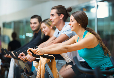 Group positive smiling working out of cycling in modern fitness club Stock Photo