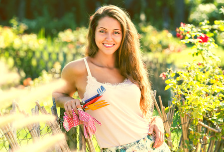Portrait of smiling long-haired young woman in summer garden