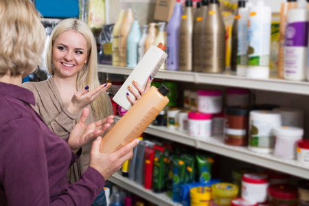 mother and adult daughter in good spirits selecting shampoo and smiling in the store