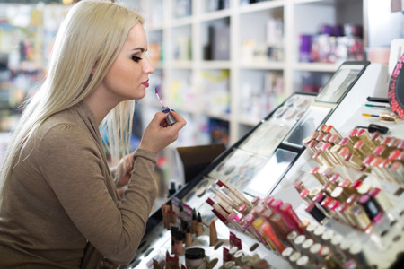 Portrait of happy young american blondie selecting lipstick in store