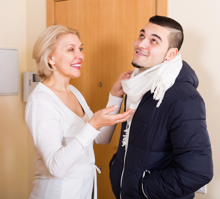 Happy senior mother helping adult son to tie a scarf at doorway