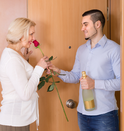 Smiling eldery woman meeting young boyfriend with flowers and wine in hands at doorway Stock Photo