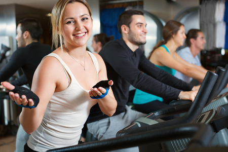 Group working out of cycling in modern fitness club Imagens