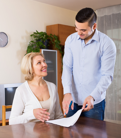 Happy young man and elderly woman sitting with banking documents indoors