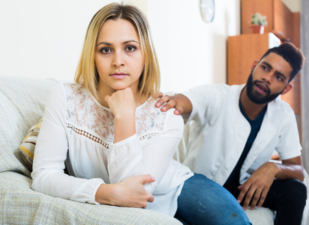 Young interracial family couple with serious faces arguing at home Stock fotó
