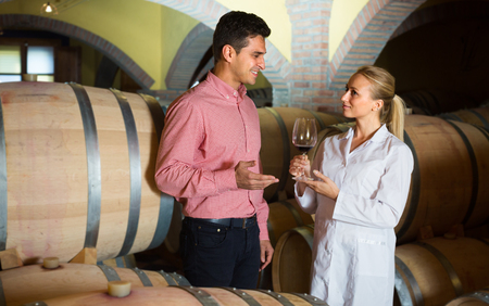 Male owner of winery having conversation with employee technician in cellar