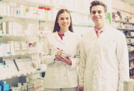 Two smiling friendly pharmacists working in luxury pharmacy
