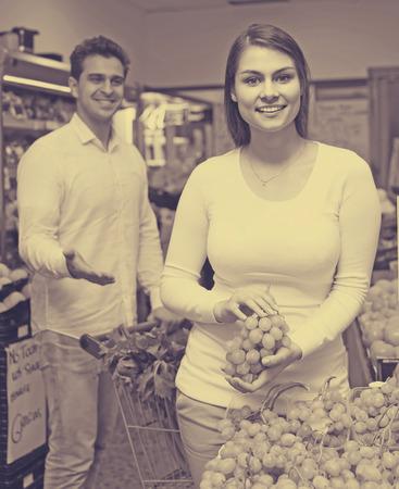 happy family couple buying fresh seasonal fruits in market Stock Photo