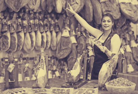 happy european female butcher with lard and meat in counter of store Imagens