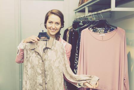 Smiling pretty girl choosing new garment in fashion store