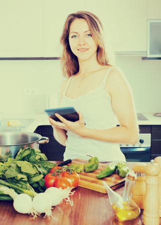 young housewife in the kitchen cooking with tablet