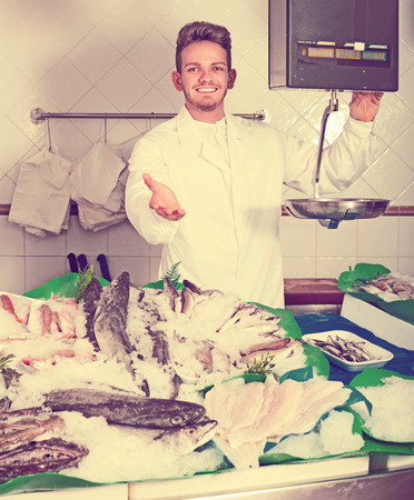 Happy young seller posing near display with cooled fish and seafood