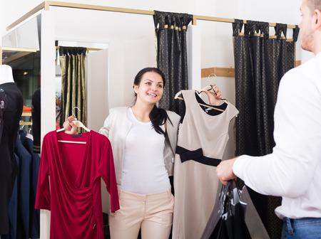 Feliz pareja ordinaria comprando vestido y blusa en la tienda de ropa