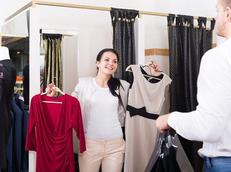 Ordinary glad couple purchasing dress and blouse at clothing shop