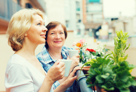 Smiling senior female pensioners relaxing with cup of coffee on balcony Standard-Bild
