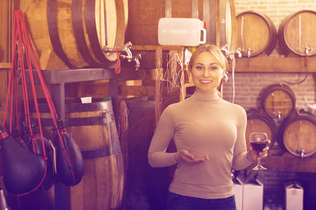 Smiling young woman tasting wine from wood in wine house