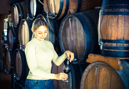 Positive smiling young woman pouring wine from wood in wine cellar Reklamní fotografie
