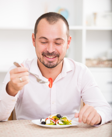 Positive young man ready to eat greek salad in office