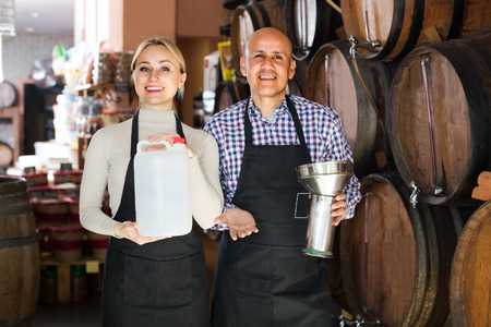 cheerful man and european woman wearing apron holding wine vessels in wine house Stock Photo