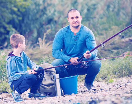 young father and teenager son fishing together in wild river