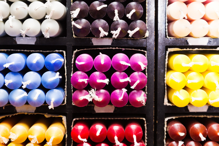 sorted: closeup view on multicolored candles sorted by color on shelf in store