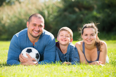 manhood: Glad son and parents lying together in football field Stock Photo
