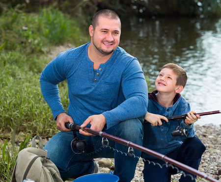 manhood: Laughing father and boy fishing with rods in summer day Stock Photo