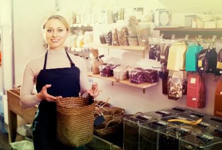 a jar stand: Happy young blond woman wearing apron and selling nuts and dried fruits in organic shop