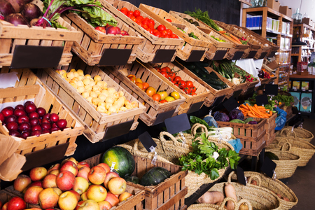 view on rustic containers with various fresh vegetables and fruits in supermarket Stock Photo