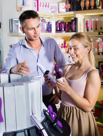 Portret van volwassen blij lachende paar kiezen van erotische speeltjes in sexshop Stockfoto